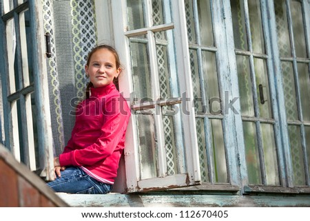 Teen-girl looks out the window rural house.