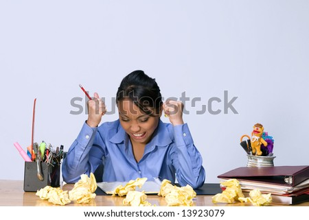 Teen girl looks stressed and angry as she sits at a desk surrounded by crumpled paper, pens, pencils, and folders. Horizontally framed photograph - stock photo