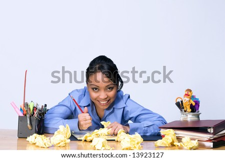 Teen girl looks stressed as she sits at a desk surrounded by crumpled paper, pens, pencils, and folders. Horizontally framed photograph - stock photo