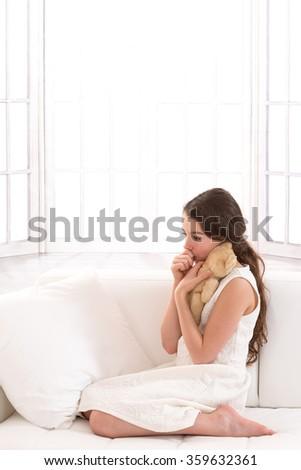 Teen  girl lovingly holding a teddy bear sucking her thumb  - stock photo