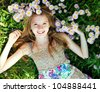 Teen girl lying in grass with flowers - stock photo