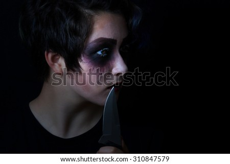 Teen girl masked in scary makeup with combat knife on black background.