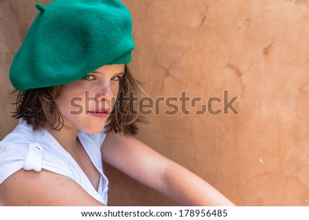 Teen Girl Mood Beret Teen girl close portrait healthy,fit, moods, serious wearing green beret hat white top. - stock photo