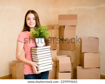 Teen girl moving house to college, holding pile books and plant - stock photo