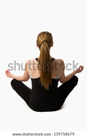 Teen girl on a white background doing yoga from behind with a long pony-tail - stock photo
