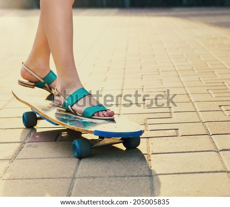 Teen girl on longboard on the street at beautiful summer evening. Close up