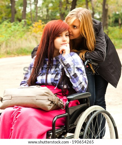 teen girl on the wheelchair with her friend in the park - stock photo