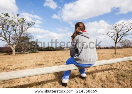 Teen Girl Outdoors Sitting Young girl teenager sitting alone  pondering thinking in park wilderness reserve - stock photo