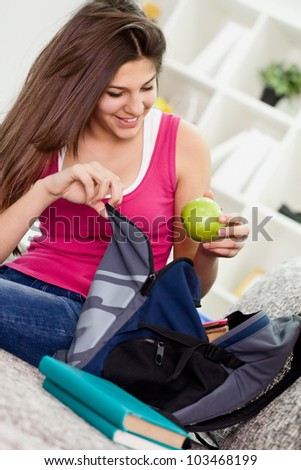 Teen girl  packing book bag preparing for school. - stock photo