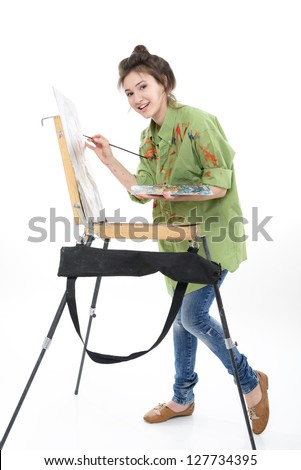 teen girl painter drawing portrait with oil paints, professional painter at work over white background - stock photo