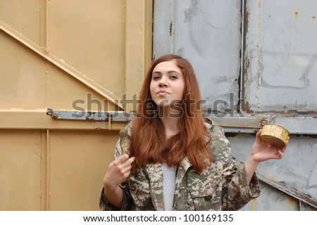 Teen girl painting old gate. Ukraine