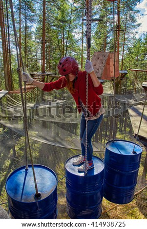 Teen Girl passing through obstacles in a Forest Rope Park Challenge - stock photo