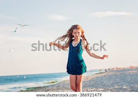 Teen girl playing on the sand near the sea - stock photo