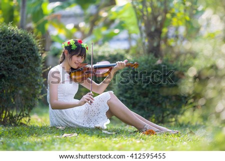Teen girl playing the violin at the grass and sunsine