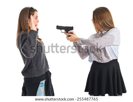 Teen girl pointing with a gun - stock photo