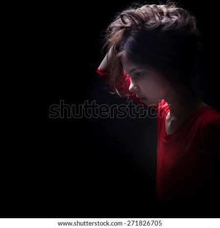 Teen girl portrait isolated on dark background - stock photo