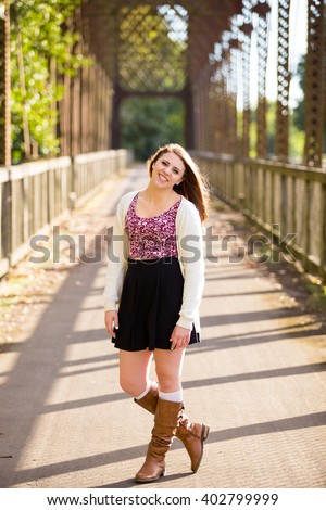 Teen girl poses for a high school senior portrait photo outdoors near a river in Eugene Oregon.