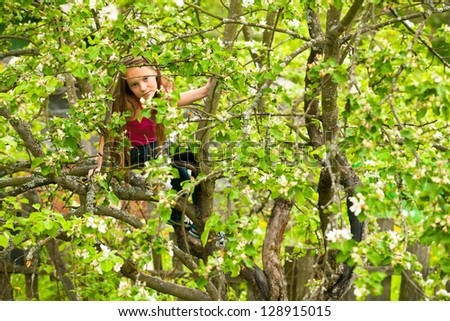 Teen-girl posing sitting on a tree in the garden. - stock photo
