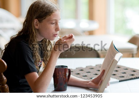 teen girl reading a book and eating soup - stock photo