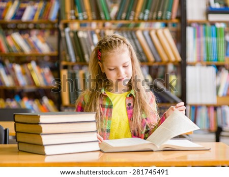 Teen girl reading a book in the library - stock photo