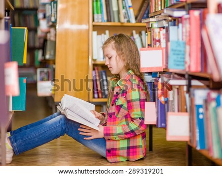 Teen girl reading a book  on the floor in the library - stock photo