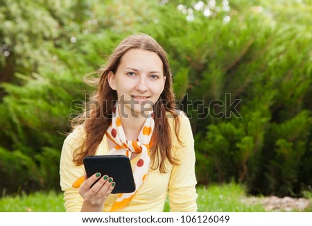 Teen girl reading an electronic book outdoors - stock photo