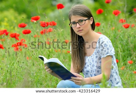 Teen girl reading book in the poppies field - stock photo