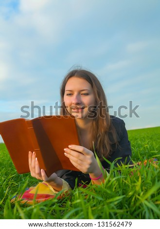 Teen girl reading the Bible laying outdoors at sunset time - stock photo