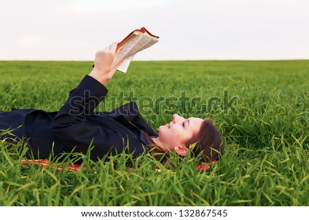 Teen girl reading the Bible outdoors at sunset time - stock photo