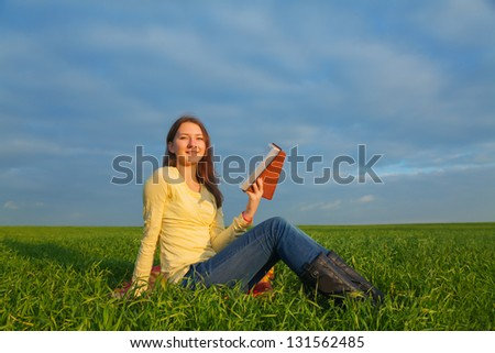 Teen girl reading the Bible sitting outdoors at sunset time - stock photo