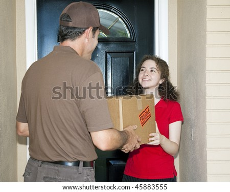 Teen girl receives package from friendly delivery man. - stock photo