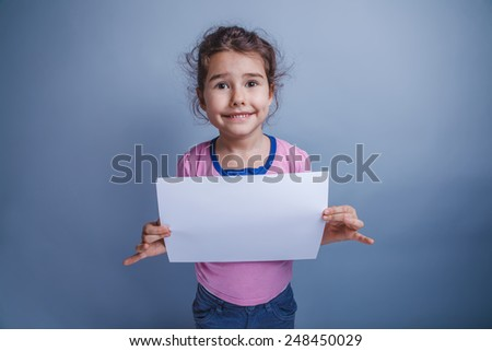 Teen girl seven years of European appearance, holding a sheet of white paper and smiling on a gray background, please - stock photo
