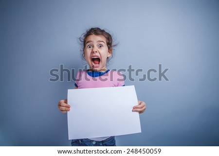 Teen girl seven years of European appearance, holding a sheet of white paper and yelling on a gray background - stock photo