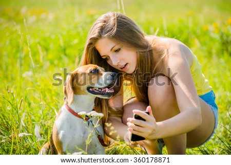 Teen girl showing something to her dog on smart-phone, outdoor in nature - stock photo