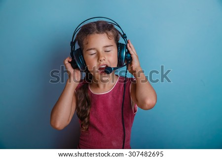 Teen girl singing in a microphone and listening to music with headphones on a blue background photo studio - stock photo
