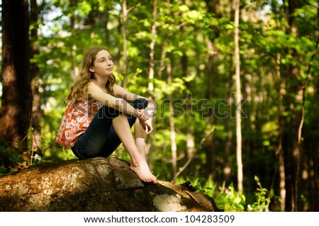 teen girl sitting in a forest daydreaming - stock photo