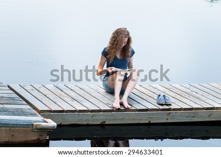teen girl sitting on a dock reading a book