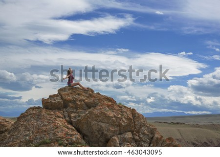 Teen girl sitting on a mountain top