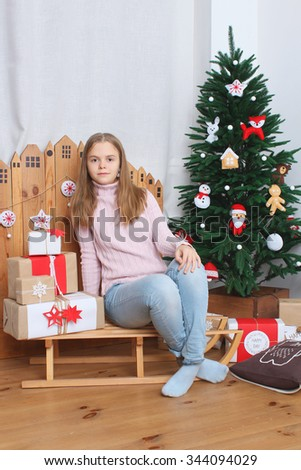 Teen girl sitting on sledge with presents and Christmas tree - stock photo