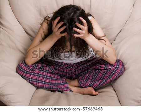 Teen girl sitting on the chair in depression and frustration crying