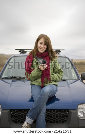 Teen girl sitting on the hood of a car, calling or texting on her cell phone. - stock photo