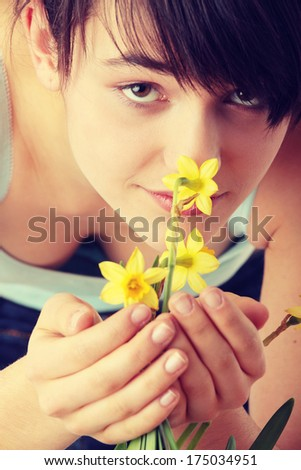 Teen girl smelling yellow spring flowers  - stock photo