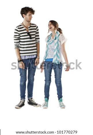 Teen girl smiles and looks up at skeptical teen boy. Vertical, isolated on white, copy space.
