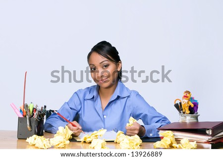 Teen girl smiles as she sits at a desk surrounded by crumpled paper, pens, pencils, and folders.  Horizontally framed photograph - stock photo