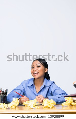 Teen girl smiling as she sits at a desk surrounded by crumpled paper, pens, pencils, and folders. Vertically framed photograph - stock photo