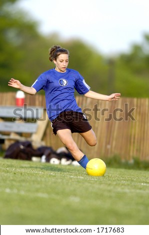 teen girl soccer player is about to kick a yellow soccer ball - stock photo