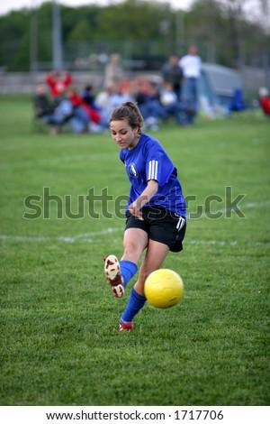 Teen girl soccer player just kicks yellow soccer ball - stock photo