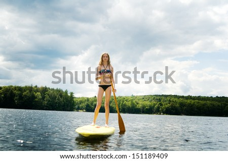teen girl stand up paddle boarding on a lake in haliburton ontario - stock photo