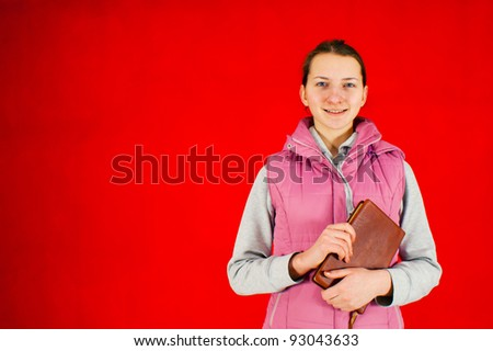Teen girl staying with a book against red background - stock photo
