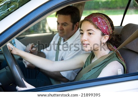 Teen girl taking driving test to get her drivers license. - stock photo